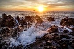 海洋敲打,日落的波浪反对岩石的 库存图片