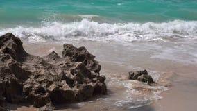 海洋泡沫似的波浪洗涤珊瑚岩石在含沙岸 股票视频