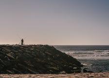 海洋海岸的渔夫 免版税库存图片