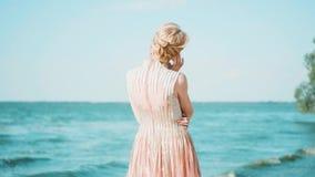 海洋海岸的逗人喜爱的妇女站立单独,冲程她的有她的手指的耳朵,拥抱单手,金发 影视素材