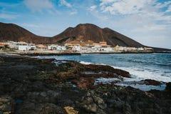 海洋海岸的Calhau村庄在红色前面上色了火山的火山口 佛得角-圣维森特岛 图库摄影