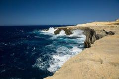 海洋的狂放的波浪飞溅戈佐岛,马耳他干燥岸  免版税库存图片