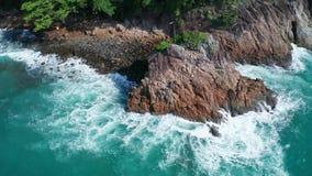 海洋的美丽的波浪和岩石热带海岸鸟瞰图与泰国旗子在岩石的峰顶 股票录像