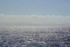 海洋的表面上的明亮的晴天和使目炫强光 库存图片
