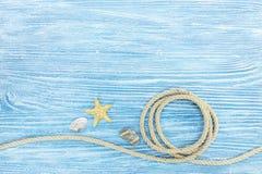 海洋石头和贝壳,在被绘的蓝色木板的绳索 库存照片