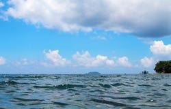 海洋风景用蓝天和水起波纹 与小船的海滨视图 免版税库存图片