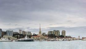 海洋驻地和小船在口岸反对城市摩天大楼在一个多云春天晚上 免版税库存图片