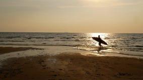 海浪人剪影有运行水表面上的冲浪板的 库存照片