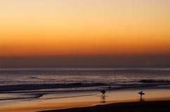从海浪出来的冲浪者在黄昏 免版税库存图片