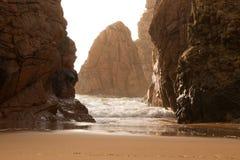 海浪和岩石在后面照在太阳之前 库存图片