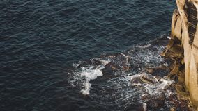 海浪和意想不到的岩石海岸鸟瞰图在索伦托 危险碰撞在与浪花和泡沫意大利的岩石海岸的海波浪 股票视频