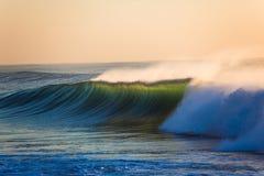 海浪浪端的白色泡沫日出背后照明颜色 库存图片