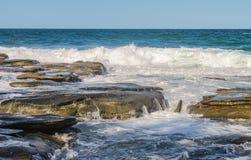 海浪碰撞反对永世老火山岩,并且水跑并且打破石头-与在天际的微小的小船 免版税库存照片