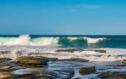 海浪碰撞反对永世老火山岩,并且水跑并且打破石头-与在天际的微小的小船 图库摄影