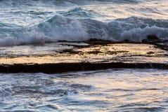 海浪飞溅在镇静岩石架子在黎明 免版税库存图片