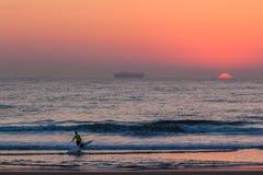 海浪滑雪独木舟男性输入的海洋太阳上升  库存图片