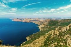 海海岸线以夏天绿色倾斜岩石岸 免版税库存图片