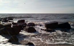 海海浪在一好日子 在前景,湿沙子,黑暗的湿石头,小波浪与飞溅和白色泡沫 库存图片