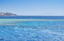 海海湾,在珊瑚礁附近停放的小船,修造在岸,在背景中运输去到公海,反对 免版税图库摄影