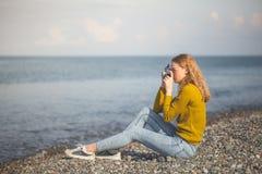 海海滩的美丽的白肤金发的女孩与一台老照相机在手中 免版税图库摄影