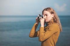 海海滩的美丽的白肤金发的女孩与一台老照相机在手中 免版税库存图片
