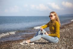 海海滩的美丽的白肤金发的女孩与一台老照相机在手中 库存图片