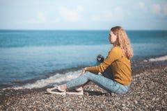 海海滩的美丽的白肤金发的女孩与一台老照相机在手中 库存照片