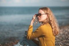 海海滩的美丽的白肤金发的女孩与一台老照相机在手中 免版税库存照片
