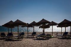 海海滩,伞轻便折叠躺椅在卡迪士中午12点阳光下 免版税库存照片