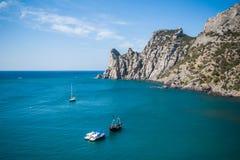 海湾、峭壁、船和游艇的看法在蓝色海的波浪 岩石小海湾用在前景的镇静水和 图库摄影