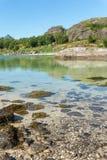 海湾、石头和绿草在夏天, Arsteinen海岛, Lofoten,挪威的绿松石水 免版税库存图片