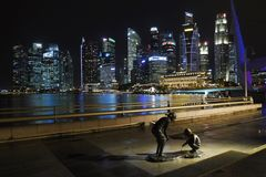 海湾海滨广场铺沙新加坡 两个孩子雕塑与摩天大楼的在背景中 库存图片