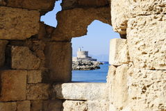 海湾的看法通过在墙壁的一个漏洞在罗得岛海岛上在希腊 免版税库存照片