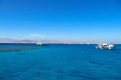 海湾的美丽的景色与漂移的小船的在岩石峭壁背景  免版税库存图片