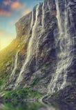 海湾geiranger挪威 在日落的壮观的瀑布在挪威 免版税库存图片