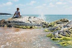 海滨坐的妇女 免版税库存照片