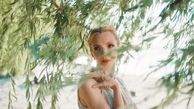 海滨的美妙的童话公主在树附近叶子,在她的肩膀和脖子上轻轻地把她的手放 影视素材