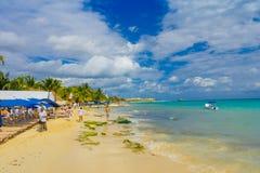 海滨del卡门,墨西哥- 2018年1月10日:坐在下遮阳伞和享用海滩的未认出的人民  免版税库存图片