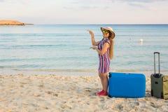 海滩、假日、假期和幸福概念-在海附近的年轻微笑的妇女指向在拷贝空间的 免版税库存图片