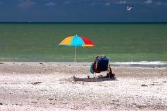海滩下读取伞 免版税库存图片