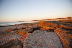 海滩不尽的形成红色岩石 免版税库存照片