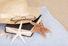 海滩书概念放松玻璃的帽子 免版税库存图片