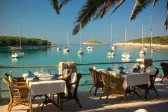 海滩俱乐部餐馆服务的表乘快艇 免版税库存图片