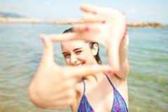 海滩做照片年轻人的框架女孩 库存图片