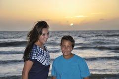 海滩兄弟青少年姐妹的日落 库存图片