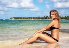海滩加勒比性感的坐的妇女 库存图片
