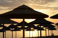 海滩反对黎明天空的背景的秸杆伞在爱琴海的岸的 库存图片