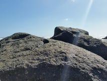 海滩向黑巨大扔石头 免版税图库摄影