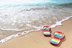 海滩含沙塑胶人字平底拖鞋的海洋 图库摄影
