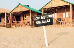 海滩含沙手段村庄和客舱与标志的不干扰我们的客人 旅馆服务概念 库存图片